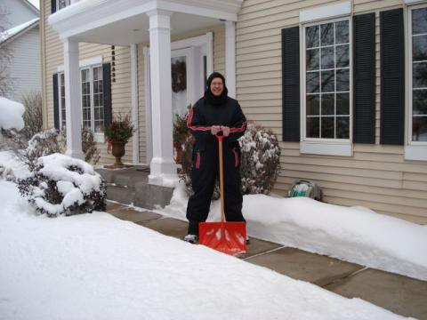 Pat with snow shovel and wearing snowsuit.