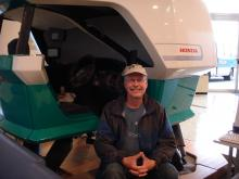 Pat poses in front of Honda driving simulator.