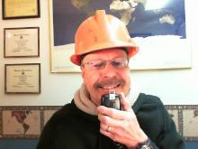 Pat talking into microphone; wearing orange hardhat