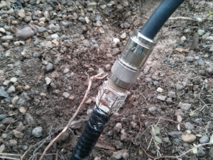 The hard line coax emerges from the earth at the base of the HF9V vertical antenna, connecting to a 75 ohm matching section.