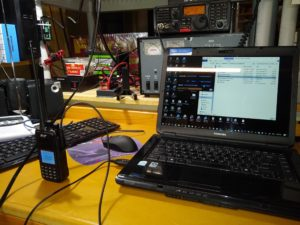 Ham station with laptop PC connected to DMR radio for programming.