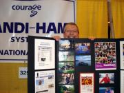 Pat behind Handiham booth display at Dayton Hamvention.