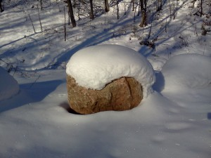 Helmet formed by snow covers a boulder in Woodbury, MN park near Wilmes Lake.